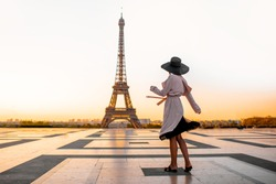 Woman dressed in coat and hat walking on the famous square with great view on the Eiffel tower early in the morning in Paris