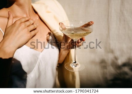 Woman dressed in white dress holding a coupe with a cocktail in sun light. Concept of an open air party. Photo stock ©