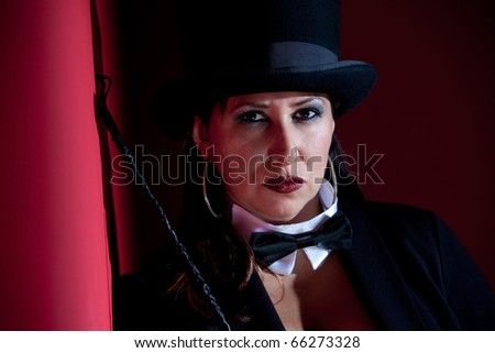 Woman dressed like a circus ringmaster with riding crop