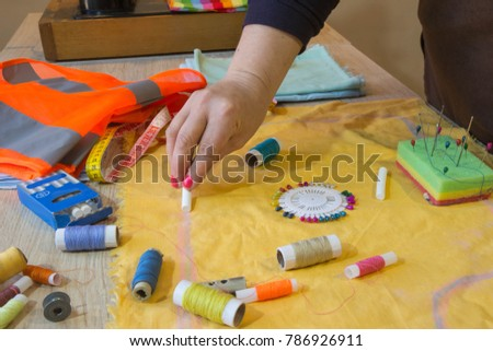 Woman dressmaker drawing tailor pattern with chalk for a clothing on the table. The outline on the fabric painted chalk. Garment industry, tailoring concept #786926911