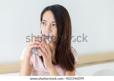 Woman drink of water and sitting on bed