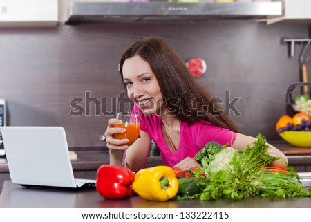 Woman drink the juice in the kitchen and looking at the computer