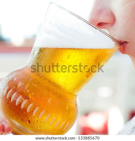 Woman drinking a beer at the pub