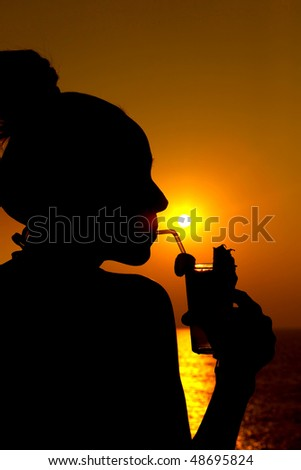 Woman drinking a cocktail over looking the ocean - silhouette.