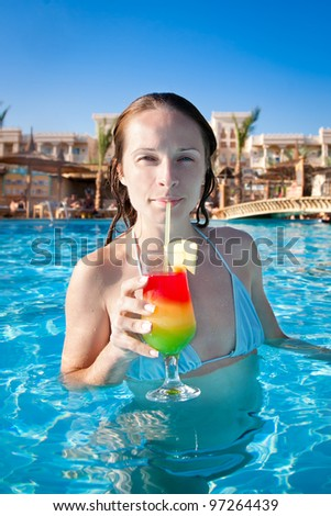 Woman drinking a fruit cocktail in blue water of swimming How to make swimming pool water drinkable