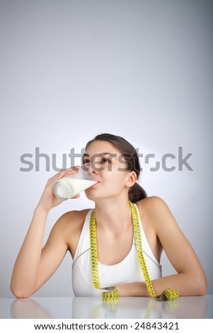 Woman drinking a glass of milk looking up