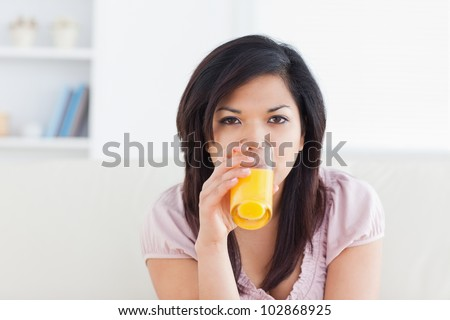Woman drinking a glass of orange juice in a living room