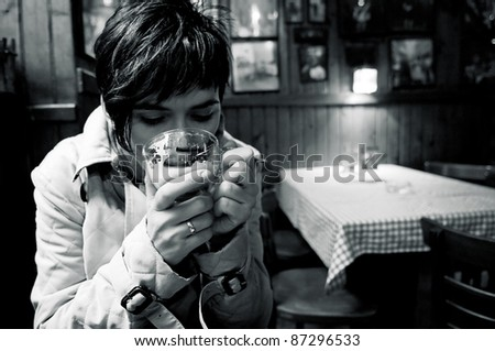 Woman drinking a hot coffee at the diner