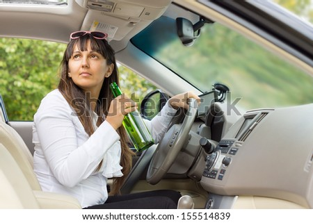 Woman drinking alcohol from a bottle behind the wheel of her car and turning to look up through the open sunroof
