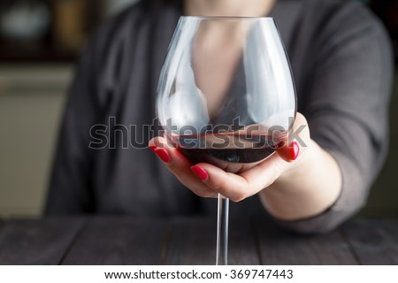woman drinking alcohol on dark background. Focus on wine glass #369747443