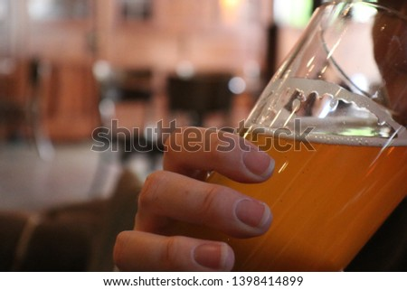 Woman drinking ale from a glass in a bar #1398414899