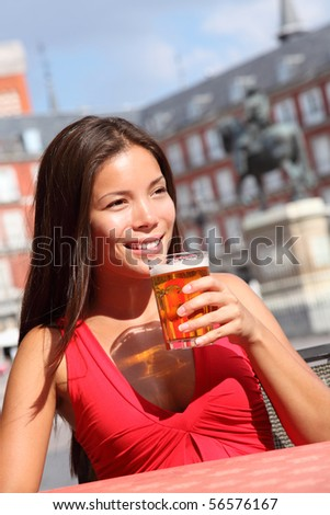 Woman drinking beer on cafe outside in Madrid, Plaza Mayor. The famous square with tourist attraction, statue of Felipe III is in the background.