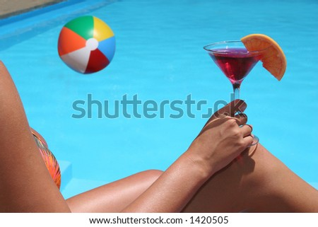 Woman drinking by a swimming pool