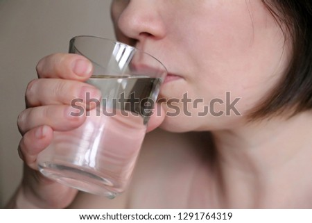 Woman drinking clean water from a glass close-up, selective focus. Concept of thirst, healthy lifestyle, water purification, skin care