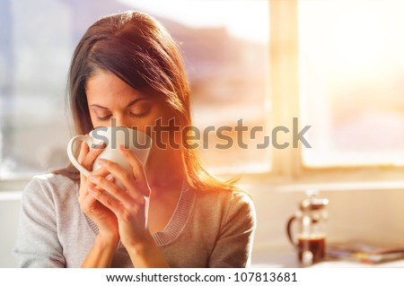 Woman drinking coffee at home with sunrise streaming in through window and creating flare into the lens. Сток-фото ©
