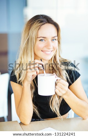 woman drinking coffee in the morning at restaurant (soft focus on the eyes)