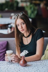woman drinking coffee in the morning at restaurant soft focus. pretty girl with cup of cappuccino. Cheerful lady enjoy and relax. Girl in a cafe with a cup of latte. Portrait of a brunette