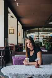 woman drinking coffee in the morning at restaurant soft focus. pretty girl with cup of cappuccino. Cheerful lady enjoy and relax. Girl in a cafe with a cup of latte. Portrait of a brunette. Beautiful