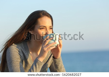 Woman drinking coffee looking away on the beach at sunset