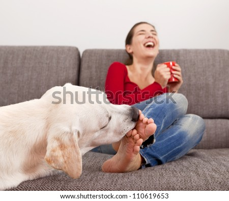 Woman drinking coffee on the sofa with her dog licking her toes