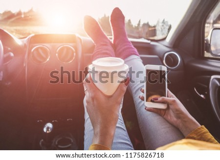 Woman drinking coffee paper cup inside car with feet warm socks on dashboard - Girl relaxing in auto trip using smartphone - Travel and trend concept - Focus on hand cup