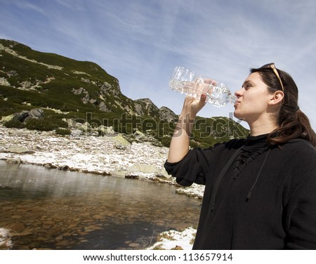 Woman drinking crystal clear water from bottle in mountain scenery