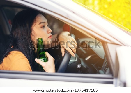 woman drinking from a beer bottle while driving car, a concept of driving intoxicated ストックフォト ©