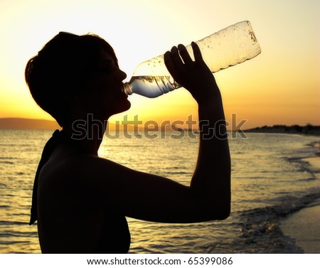 Woman drinking from a Water Bottle at Sunset - stock photo