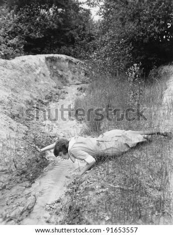 woman drinking from tiny stream