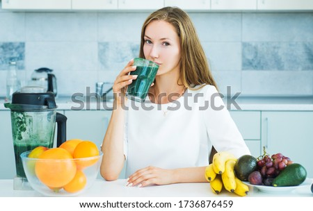 Woman drinking green spirulina in a white kitchen. Detox. Perfect body and calorie. Vegan meal diet at home. Food supplements. organic food and vitamin. Fitness and dieting. Spirulina, Superfood Foto stock ©