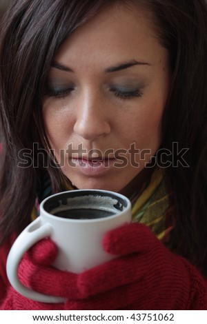 Woman drinking hot coffee during winter