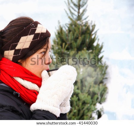 Woman drinking hot coffee or tea outdoors in winter. The background is an ice wall.