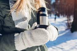 Woman drinking hot tea holding vacuum flask in winter park. Drinks to warm up in snowy frosty weather outdoors