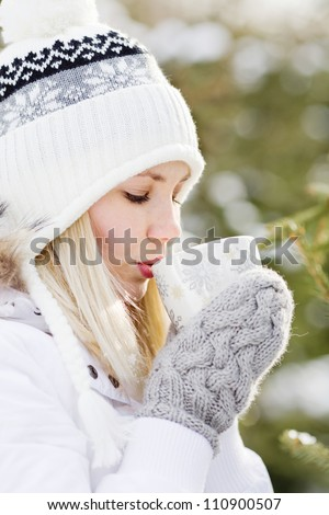 Woman drinking hot tea in the winter forest, vertical frame - stock photo