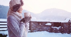 Woman drinking Hot Tea or Coffee from Festive Cup with Snowy Mountain View on Background. Beautiful Girl Enjoying Winter Morning or Evening Outdoors under the snowfall. Christmas Holidays