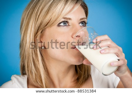 Woman drinking milk on a blue background