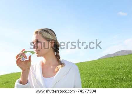Woman drinking natural water in green field