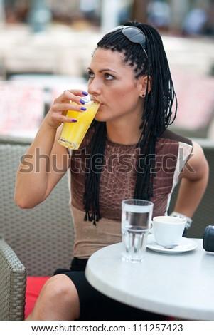 woman drinking orange juice in bar terrace