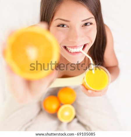 Woman drinking orange juice smiling showing oranges. Young beautiful mixed-race Asian / Caucasian model.