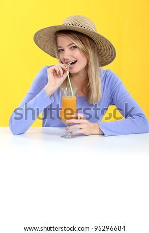 Woman drinking orange juice through straw