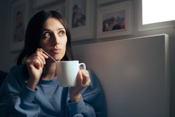Woman Drinking Tea for Insomnia Sitting in her Bedroom. Sleepy young person having a calming homeopathic herbal beverage before sleep