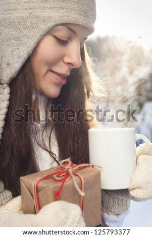 woman drinking tea, holding gift in hand on background of winter landscape, outdoor
