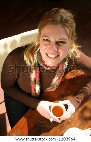 Woman drinking tea while the sun shines through the window
