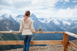 Woman drinking warm tea in the rustic wooden terrace on mountain, alpine view, snow on hills. Dombay, Karachay-Cherkessia, Caucasus, Russia.