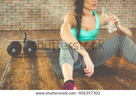 Woman drinking water after training on the sport mat