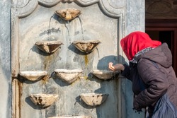 woman drinking water from a historic fountain