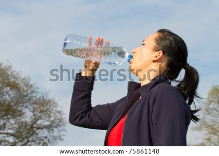 Woman drinking water from the bottle outdoor