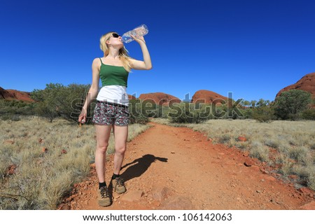 Woman drinking water in australian outback, Northern Territory