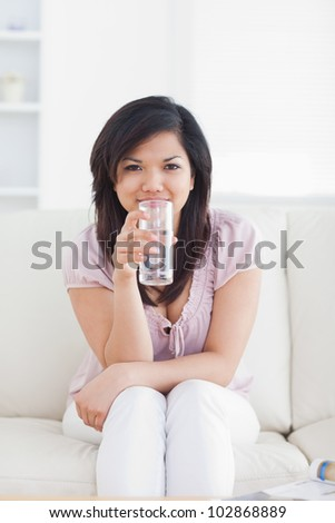 Woman drinking water while sitting in a couch in a living room