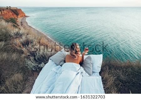 Woman drinking wine enjoying view on beach landscape while relaxing in bed on mountain in sunset on the edge of Earth. Calm and quiet wanderlust concept moment when person feels happiness and freedom. ストックフォト ©